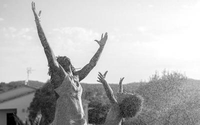 Foto em preto e branco de criança e mulher com as mãos erguidas comemorando.