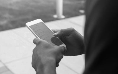 Foto em preto e branco de adolescente mexendo no celular - proteção de dados