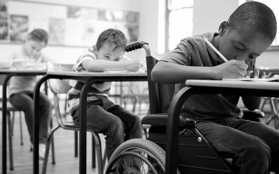 Foto em preto e branco de escola com educação inclusiva: três crianças sentadas em carteiras escrevendo, uma delas é uma pessoa com deficiência