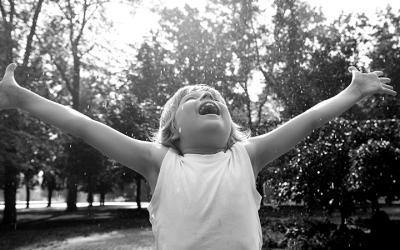 Foto em preto e branco de criança com os braços estendidos comemorando