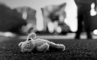 Foto em preto e branco de urso de pelúcia jogado no chão