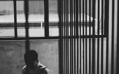 Foto em preto e branco mostra jovem em meio a um monte de grades do sistema socioeducativo