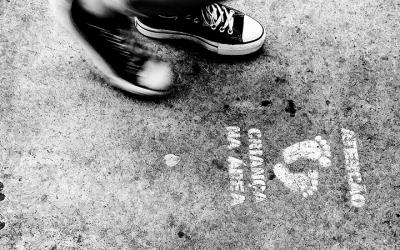 Foto em preto e branco mostra pé de criança próximo a desenho de pés no chão com o texto: atenção, criança na área
