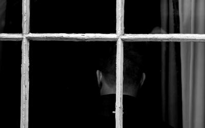 Foto em preto e branco de pessoa de costas. Em primeiro plano, grades.