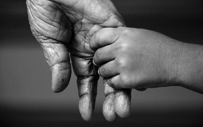 Foto em preto e branco de criança dando a mão para uma pessoa idosa