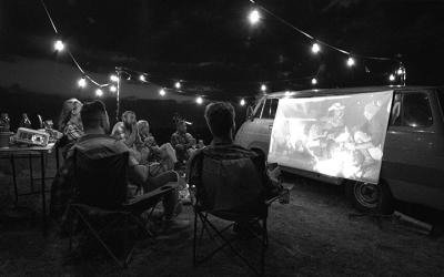Foto em preto e branco de grupo de amigos sentados em roda assistindo um filme projetado em tela estendida na lateral de uma kombi