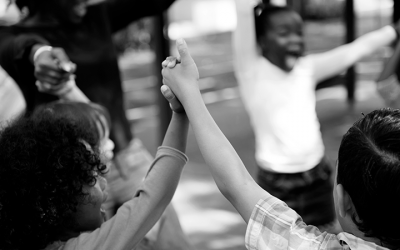 Foto em preto e branco de crianças em roda com as mãos dadas levantadas, celebrando