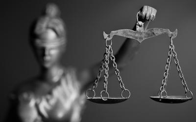 Foto em preto e branco da estátua que representa a Justiça: uma mulher, com os olhos vendados segurando uma balança.