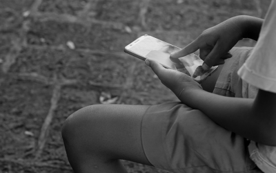 Foto em preto e branco de criança mexendo no celular