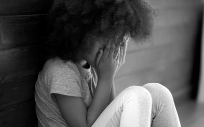 Foto em preto e branco mostra menina sentada com as mãos escondendo o rosto. Representa criança triste com relação a exploração sexual infantil