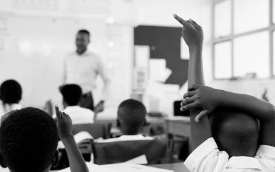foto em preto e branco de sala de aula em escola. em primeiro plano, criança com o braço levantado e, ao fundo, professor e colegas