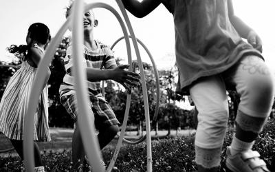 Foto em preto e branco de 3 crianças brincando com bambolês