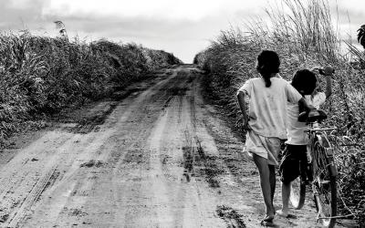 Foto em preto e branco mostra duas crianças em situação de vulnerabilidade empurrando uma bicicleta por uma estrada de terra