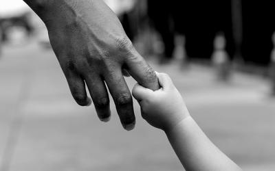 Foto em preto e branco de mão de criança segurando o dedo indicador de adulto