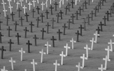 Foto em preto e branco de várias cruzes, em alusão a cemitério