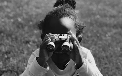 Foto em preto e branco de menina com binóculos