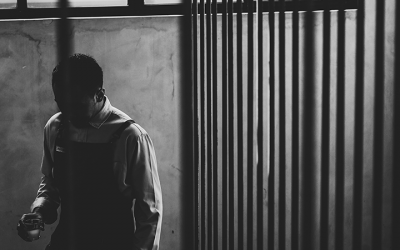 Foto em preto e branco de adolescente. À direita grades representando o sistema socioeducativo