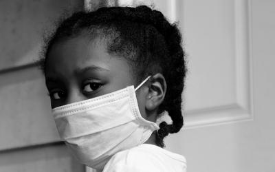 Foto em preto e branco de criança com máscara de proteção