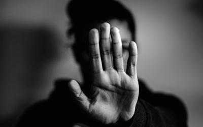 """Foto em preto e branco de adolescente com a mão aberta em frente ao rosto como um sinal de """"pare"""""""