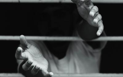 Foto em preto e branco de adolescente com as mãos estendidas para fora de grade
