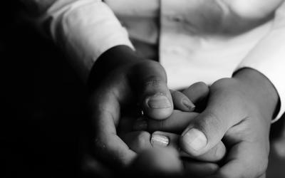 Foto em preto e branco mostra adulto segurando mão de adolescente, representa cuidado com adolescentes no sistema socioeducativo em meio à pandemia