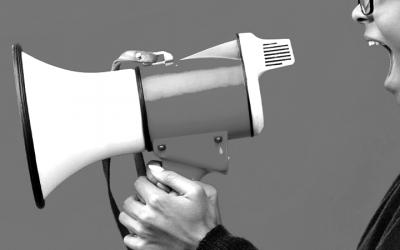 Foto em preto e branco de adolescente segurando um megafone. Representa a denúncia de violações ao sistema socioeducativo durante a pandemia
