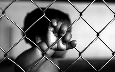 Foto em preto e branco de criança com a mão segurando grade