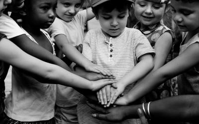 Foto em preto e branco de crianças dando as mãos