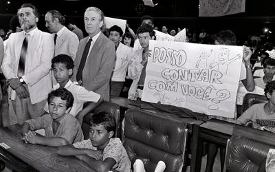 Foto em preto e branco mostra crianças do Movimento Nacional de Meninos e Meninas de Rua (MNMMR) ocupando o Congresso em sessão simbólica. Crianças seguram cartaz escrito: posso contar com você? | ECA