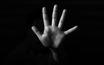 Foto em preto e branco mostra mão aberta em sinal de pare. Simboliza a prevenção de violências durante a pandemia