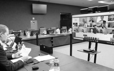 Foto de sessão do CNJ por videoconferência. Na sala de sessão do CJ, à esquerda presidente sentado lê um documento. À sua frente uma tela com várias pessoas em videoconferência