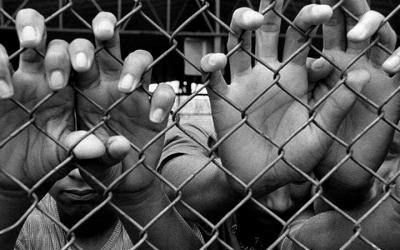 Foto em preto e branco mostra vários adolescentes com as mãos segurando grades