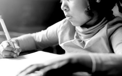 Foto em preto e branco mostra criança escrevendo no caderno na escola
