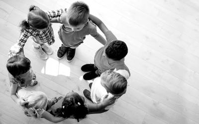 Foto em preto e branco mostra crianças abraçadas em círculo representando união em defesa da primeira infância