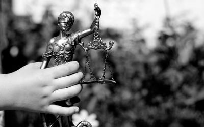 Foto em preto de mão de criança segurando estátua da justiça