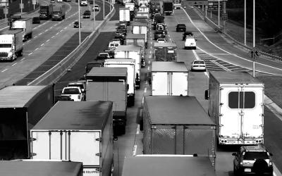 foto em preto e branco de vários caminhos em rodovia, fazendo referência à poluição do ar por veículos pesados