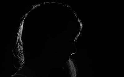 Foto em preto e branco mostra silhueta de criança com o rosto triste