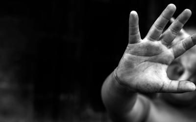 Foto em preto e branco de criança com a mão estendida em frente ao rosto