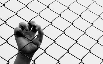 foto em preto e branco de mão de adolescente segurando grade