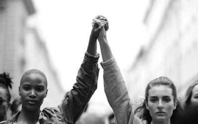 Foto em preto e branco de duas mulheres com as mãos dadas erguidas em protesto
