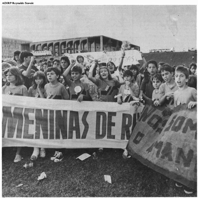 Foto em preto e branco mostra várias crianças segurando faixas em frente ao Congresso Nacional
