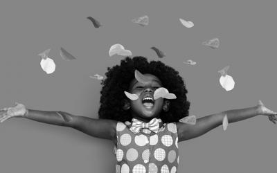 Foto em preto e branco mostra criança com os braços estendidos comemorando enquanto caem confetes