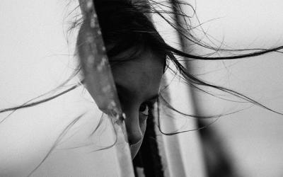 Foto em preto e branco mostra menina com metade do rosto para fora da janela do carro com um olhar assustado