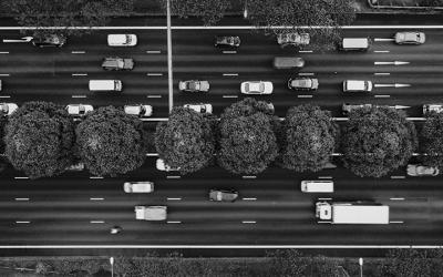 Foto em preto e branco vista de cima mostra trânsito com vários carros e caminhões
