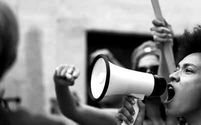 Foto em preto e branco de mulher com um megafone