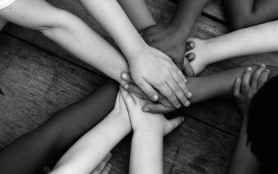 Foto em preto e branco mostra várias mãos, uma em cima da outra, simbolizando união, trabalho em equipe