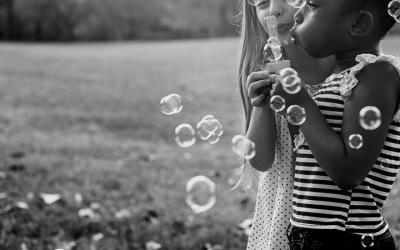 Foto em preto e branco mostra duas meninas brincando com bolhas de sabão