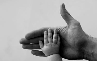 Foto em preto e branco mostra mão de bebê apoiada em mão de adulto representando cuidado com as crianças durante as eleições