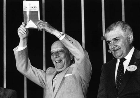 Foto em preto e branco mostra Ulysses Guimarães sorrindo com a mão erguida segurando a nova Constituição Federal