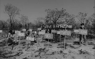 """Foto em preto e branco. Jovens de máscara, com placas escritas: ONÇA, MACACO, TATU, TUCANO, COBRA, PREGUIÇA, CATIRU, entre outras. No fundo, uma grande placa escrita """"Salve a Amazônia""""."""